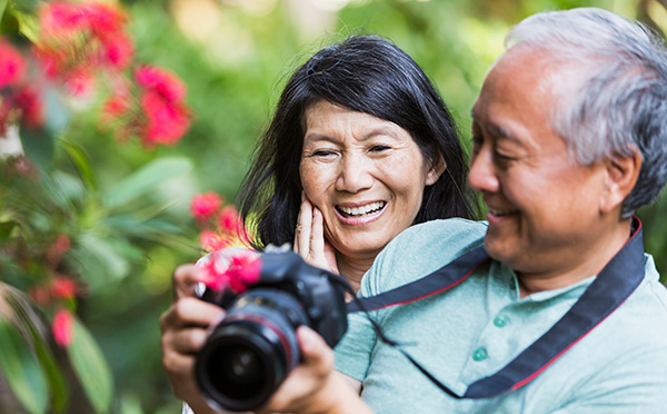 Couple Smiling together after taking a photo of flowers