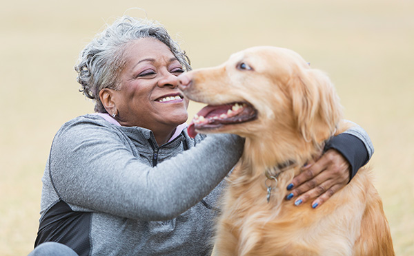 Woman smiling and hugging her pet golden retriever